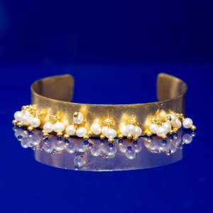 Dangle Pearl Cuff on a blue reflective surface.