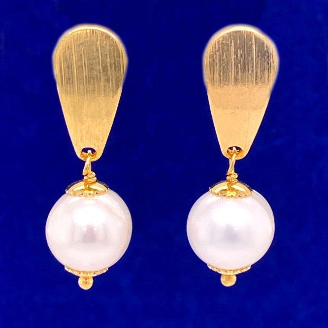 Single Pearl Dangle Earrings on a blue background.