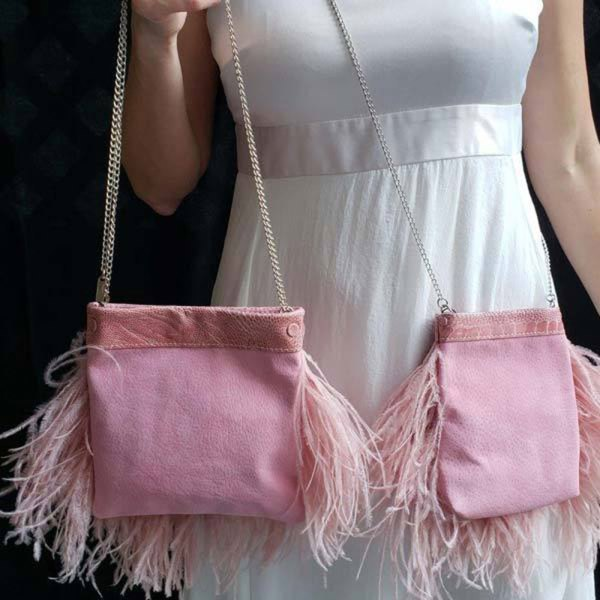Model holding two Blush Ostrich Feather Handbags showing back side of bag without feathers.