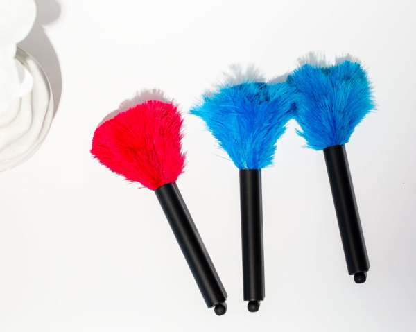 Turquoise and Pink Mini Ostrich Feather Dusters laying on a white table.