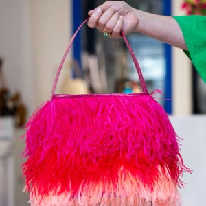 Hot Pink, Red, Coral Shayleen Purse held in a models hand by the handle.