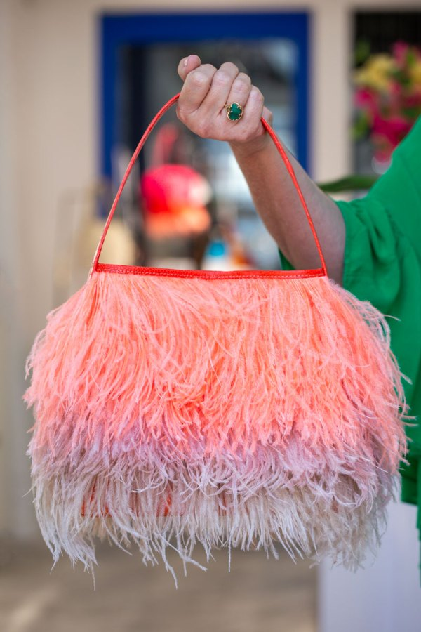 Coral/Blush Shayleen Purse held in a models hand by the handle.