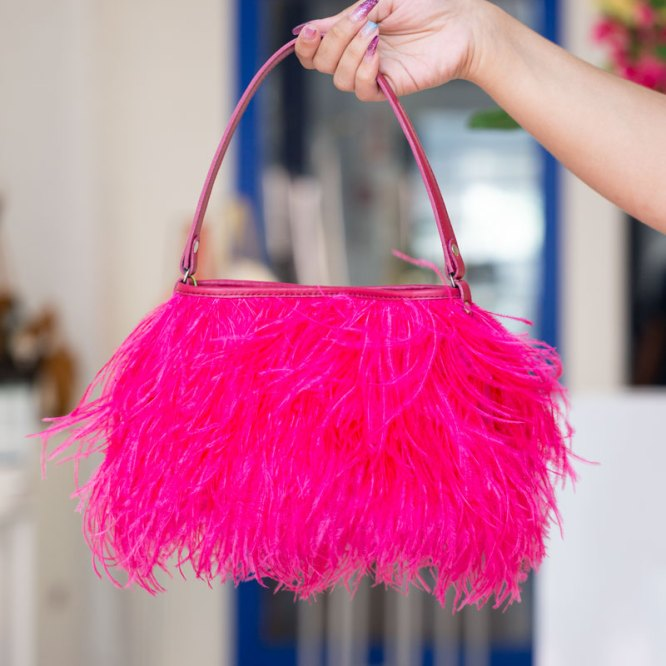Hot Pink Yumi Bag held in a models hand.