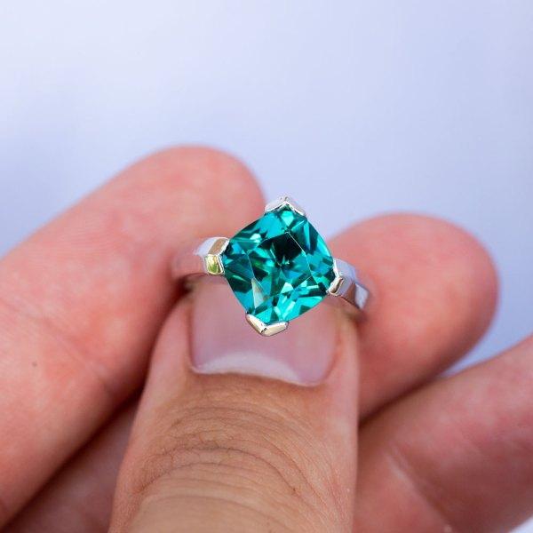 Caribbean Blue Quartz Cushion Cut Ring held between the fingers of a model.