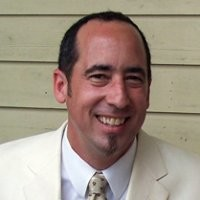 Image of Blue Krewe CEO Geoff Coats smiling and wearing a white suit and tie.