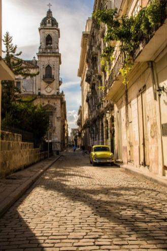 A street in Havana, with a church and a yellow vintage car