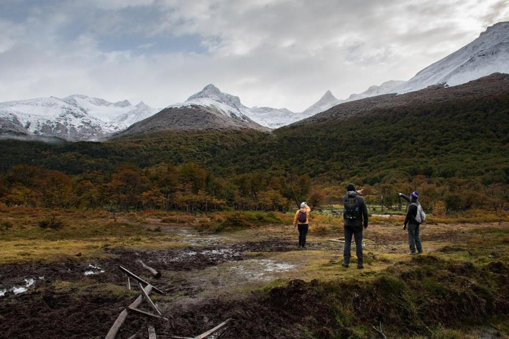 Three people on the muddy meadow, each showing to other direction. Snowy mountains in the distance