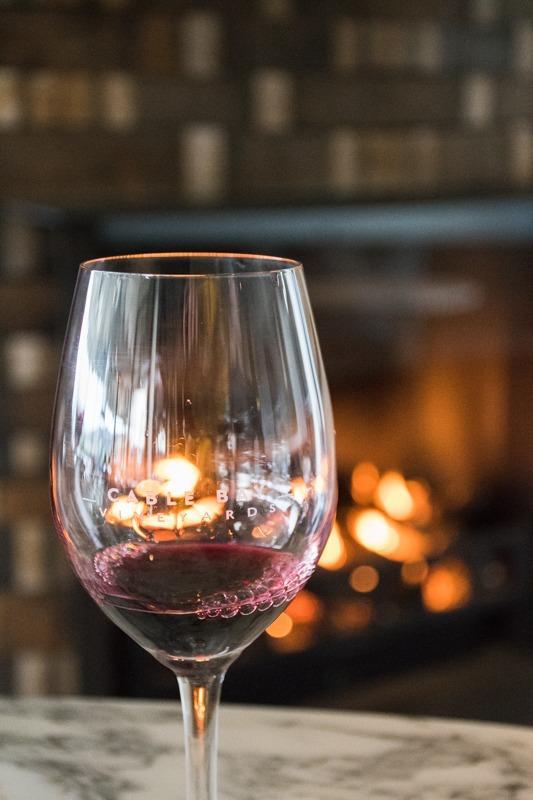 Rdeče vino v kozarcu, v ozadju zamegljen prižgan kamin.