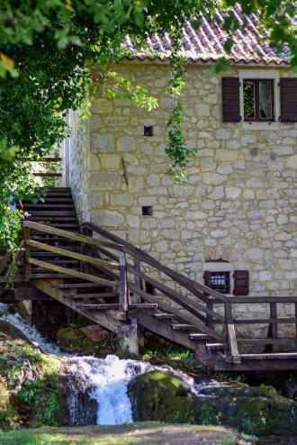 Del bele opečnate stavbe in lesene stopnice, ob njih pa potoček - mlin v NP Krka
