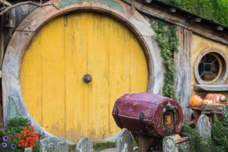 Miniaturni nabiralnik pred vhodom v hobit luknjo z rumeni okroglimi vrati