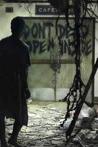 A man in silhouette wanders down a hospital corridor in shambles.