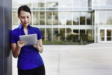 Woman using tablet outside office building