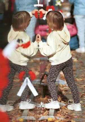 A young girl presses a flower next to the name of a relative who died in the Vietnam war. This photo was taken on Veterans Day, 1999.