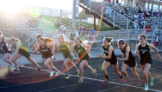 High school runners compete as the sun sets at Floyd County High School.