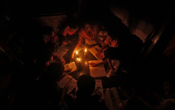 A teacher conducts a lesson for students in the light of kerosene lamps and a candle during a power-cut inside a house in Kolkata J