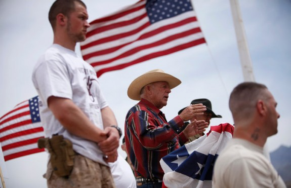 Cliven Bundy enjoying he limelight on stage and guarded by armed supporters. (John Locher/Las Vegas Review-Journal via Associated Press)