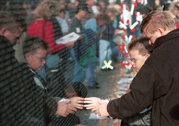 Remembering: A son and a grandson visit the Vietnam Memorial Wall in Washington, DC. Their father and grandfather's name is on the wall. (Photo by Doug Thompson)