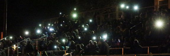 Fans use their smartphones to provide light after the field went dark.
