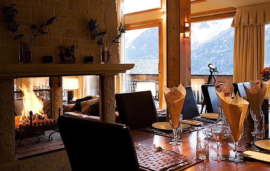 Chalet Serena Dining Table Fireplace lit mountains yoga retreat chamonix mont blanc france hiking retreats spa healthy food alps vegan vegetarian hot tub relax fitness