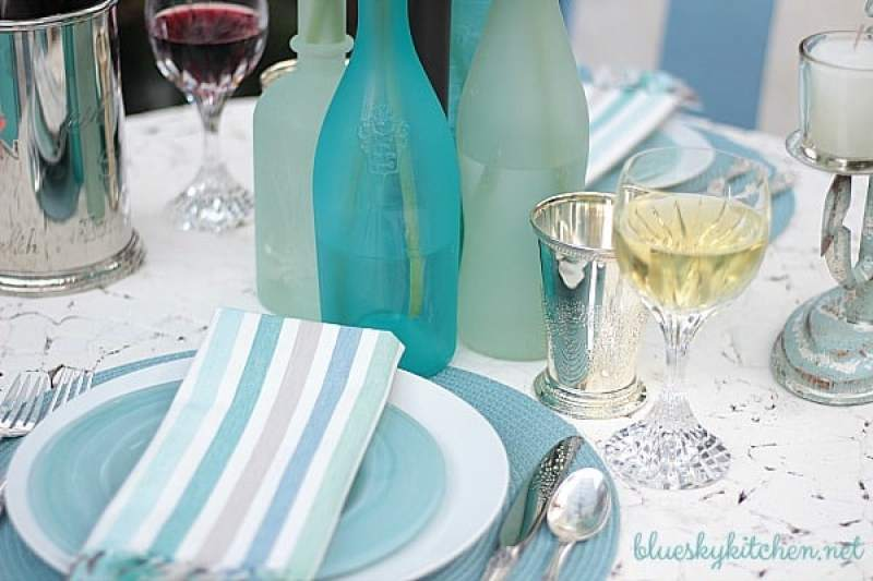 Romantic Coastal Alfresco Tablescape creates a lovely evening dining experience. DIY sea glass bottles add to the romantic setting.