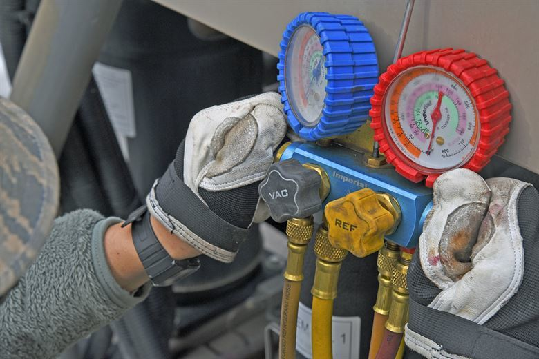 technician checking pressure on air conditioner