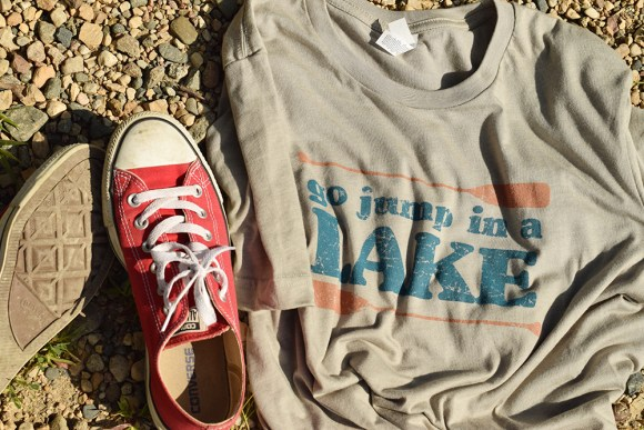 Go Jump in a Lake t-shirt with red Converse shoes on lakeshore rocks