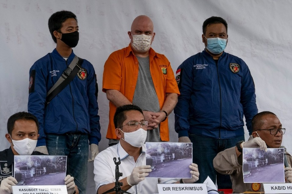 Russ Medlin (standing centre), an American wanted by the US Federal Bureau of Investigation, was paraded by Indonesian police following his arrest on child-sex charges - BAY ISMOYO / ©AFP