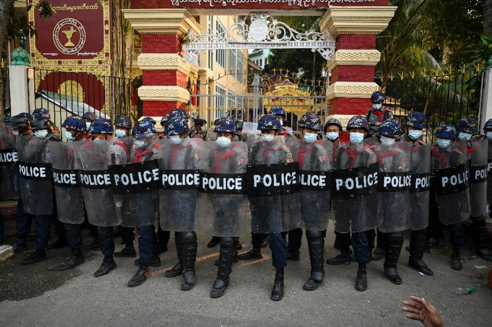 Myanmar police stand guard at the entrance gate of a Buddhist monastery where pro-military supporters took shelter after clashes in Yangon - YE AUNG THU / ©AFP
