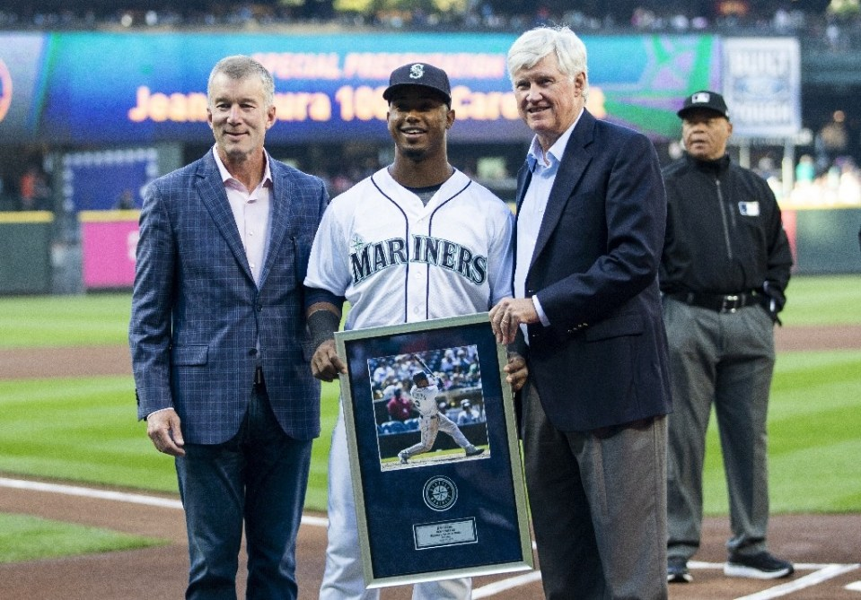 Seattle Mariners President Kevin Mather, left and CEO John Stanton pose with Jean Segura #2 of the Seattle Mariners as he is presented with a plaque commemorating his 1,000th career hit before the game against the Baltimore Orioles at Safeco Field on September 3, 2018 in Seattle, Washington - Lindsey Wasson / ©AFP