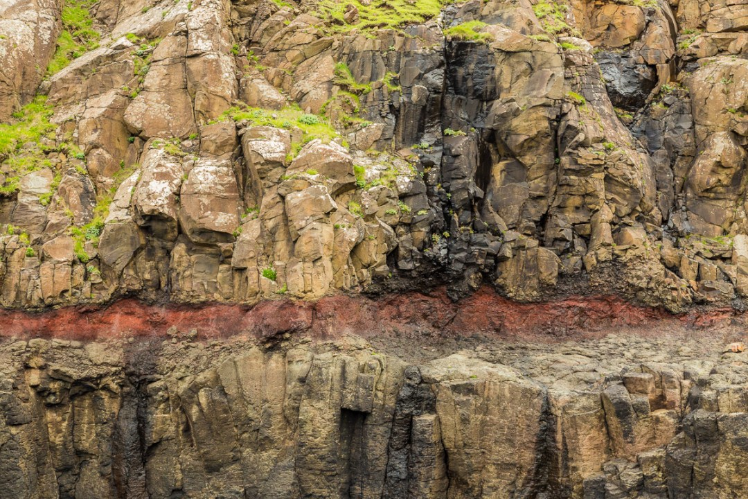 The red layer of clay in between basalt on Suduroy, Faroe Islands.