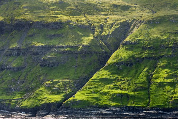The land vehicles on the road provide a measure of scale for the formations of the island mountains Near Tjornuvik, Faroe Islands.