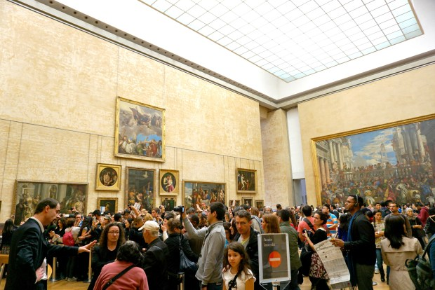 A crowd of people taking a picture of the Mona Lisa