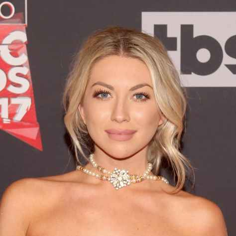 Stassi with loose, face framing curls and a matte pink lip