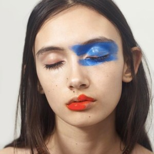 Artsy Makeup: Alined red lip with orange undertone and cool cobalt blue cream shadow smeared on one eyelid and under-eye.