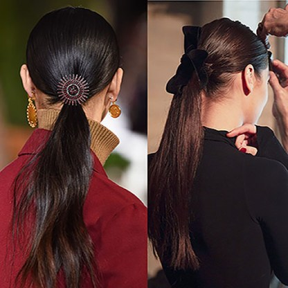 ponytails. One is held with a circular, ornate clip, the other one with a velvet ribbon.