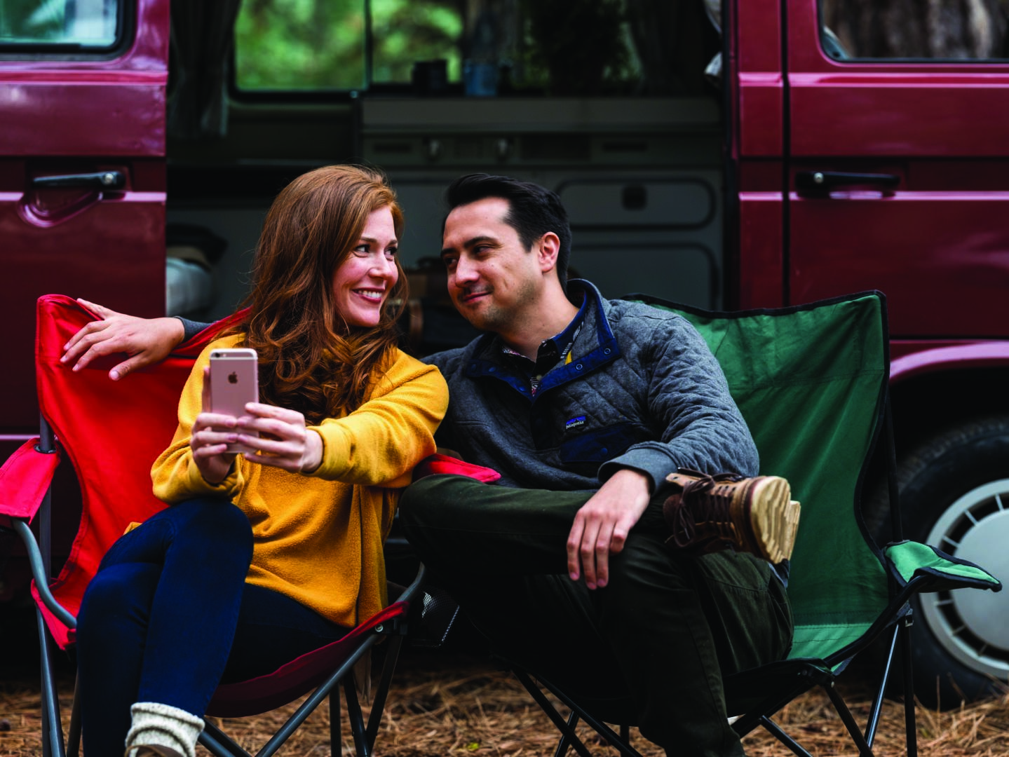 Image of a girl taking a selfie camping with a guy