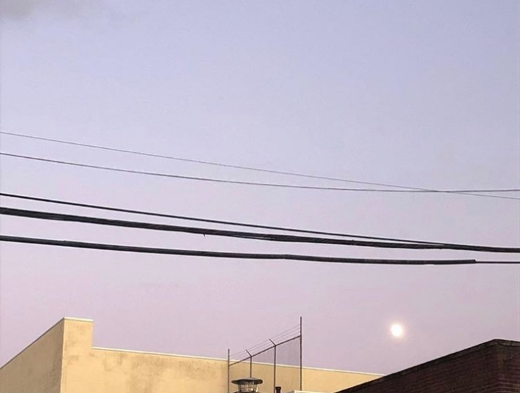 Image of the moon at dusk, above a building