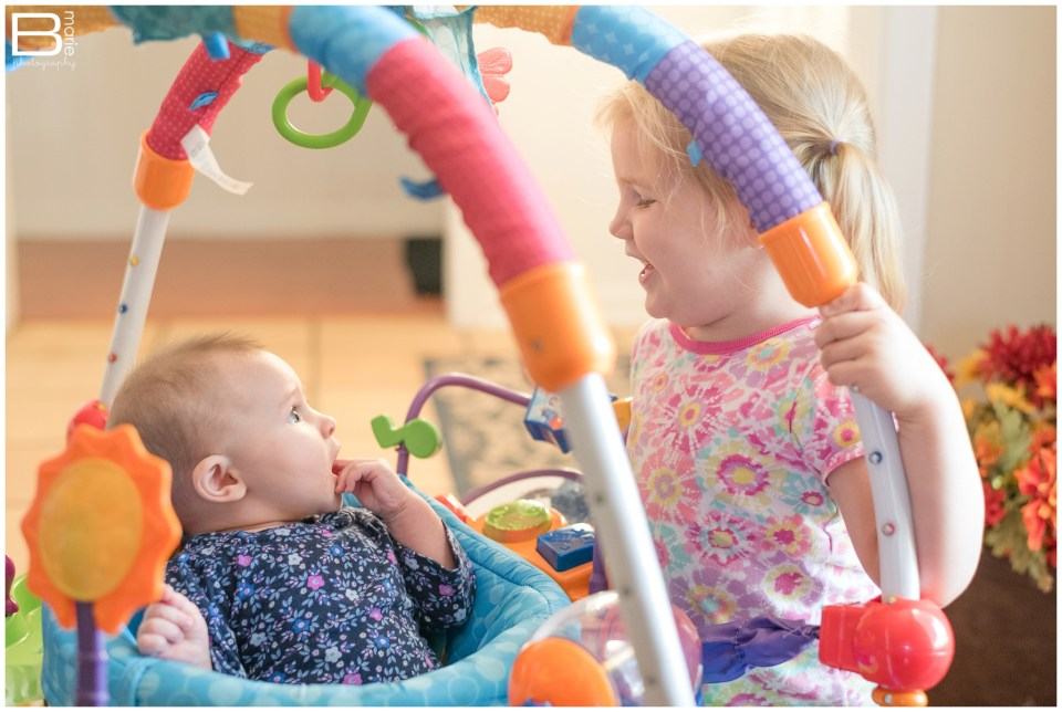 Nacogdoches photographer monthly photo project of daughters Peanut & Pumpkin playing together with activity bouncer seat