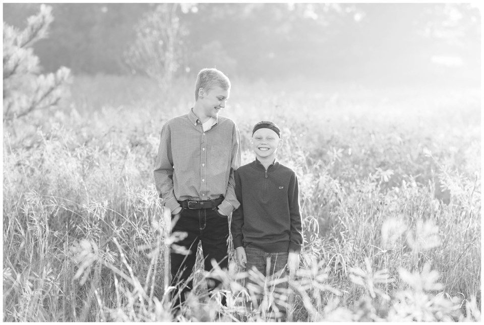 Kingwood photographer's sunrise session in tall, light-colored grass with family of four