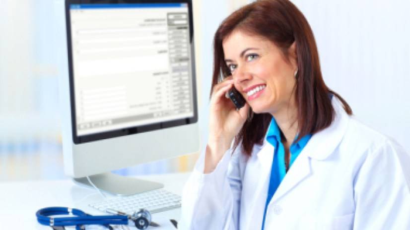 Smiling medical doctor woman with computer and telephone.