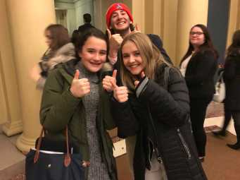 Delegates Abby Mynahan '19 and Emma Hastings '19 give the thumbs up before the opening ceremony, as Jared Heller '19 photo bombs. Photo by David Cutler '02.