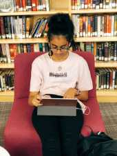 Kusumitha Mallidi '19 listens to music while working on her iPad.
