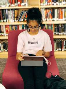 Kusumitha Mallidi '19 listens to music while working on her iPad.