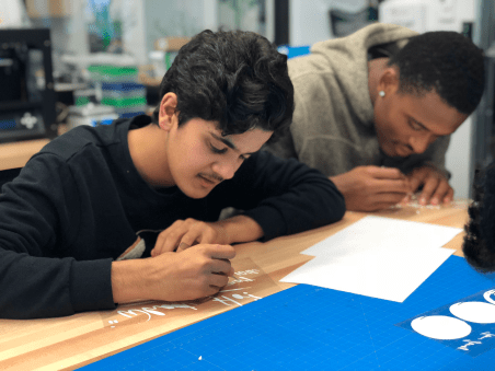 Rakan Alomran '19 peeling off stickers for STEAM Lab. Photo By Sita Alomran '19.