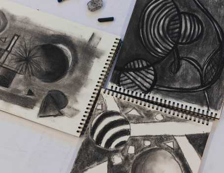 In Drawing, students draw shapes using charcoal pencils, sticks, and vine.
