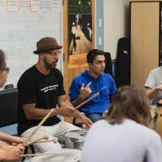 Guest Artist Marcus Santos leads the Upper School Ensemble in a Brazillian Maculele drum session.