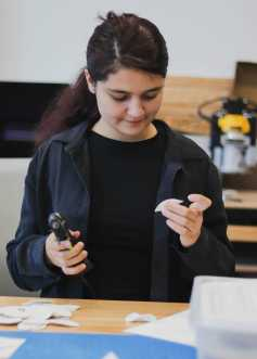 Liyanah Naji '23 uses hot glue to piece together her model.
