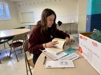 Megan Stander '20 flips through a book at the Invoicing table. Photo by Edan Zinn '23. Photo by Edan Zinn '23.