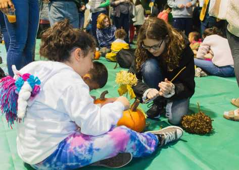 Myer Kriss '26 and Katherine Knox '26 use leaves to decorate a pumpkin.