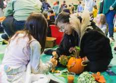 Hebe Qiang '23 collaborates with a Lower School student to decorate their pumpkin.
